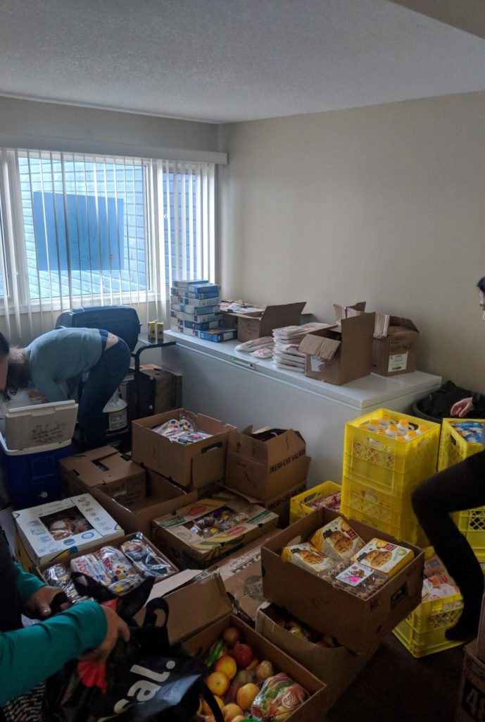 Several boxes on the floor of a white room full of food. Three people are sorting the food in the boxes.