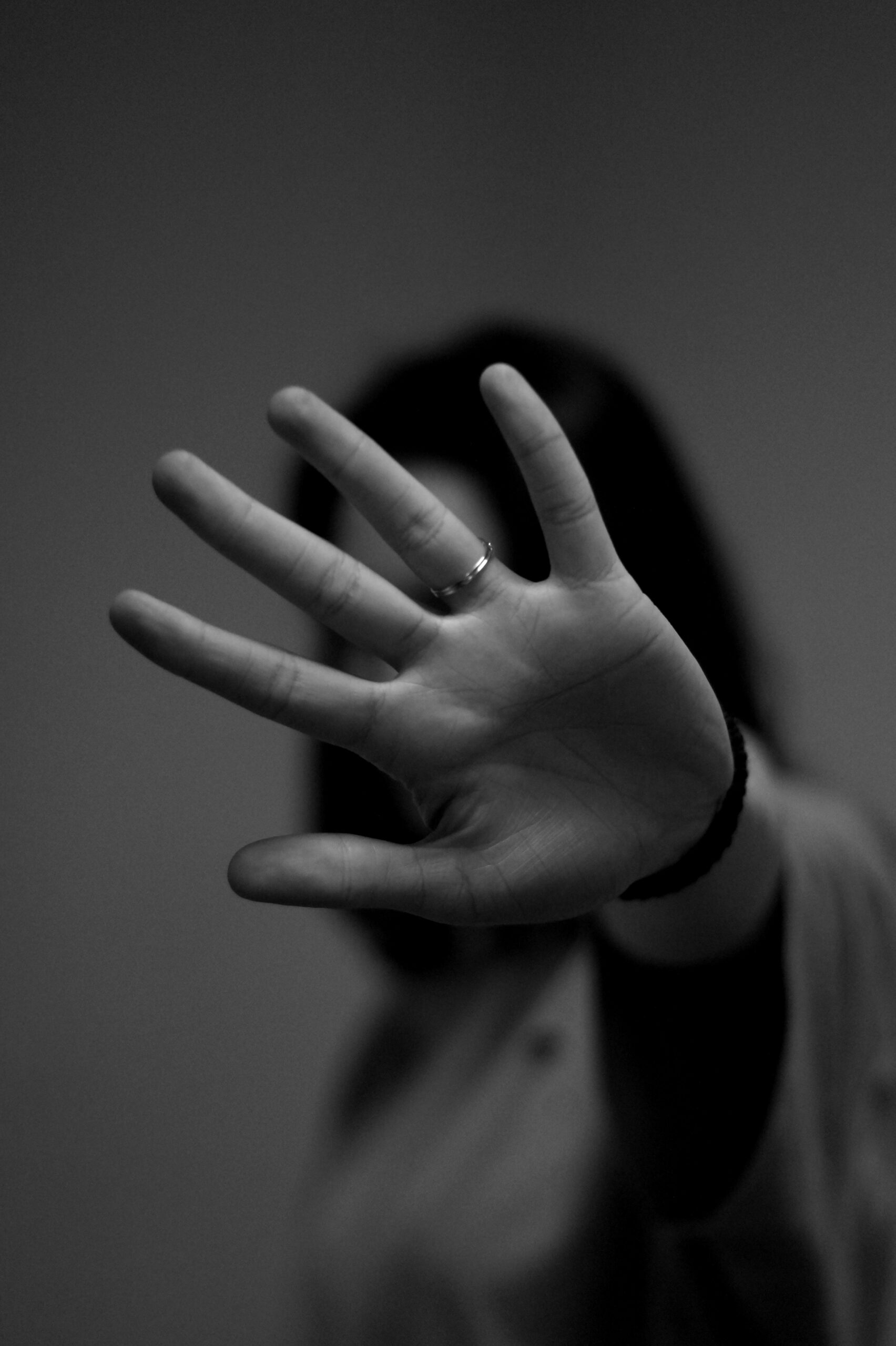 A woman with her hand in front of her blocking her face. Grey-scaled. Photo by Mattia Ascenzo on Unsplash.