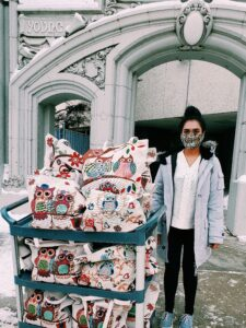 Young woman standing next to a cart full of gift bags